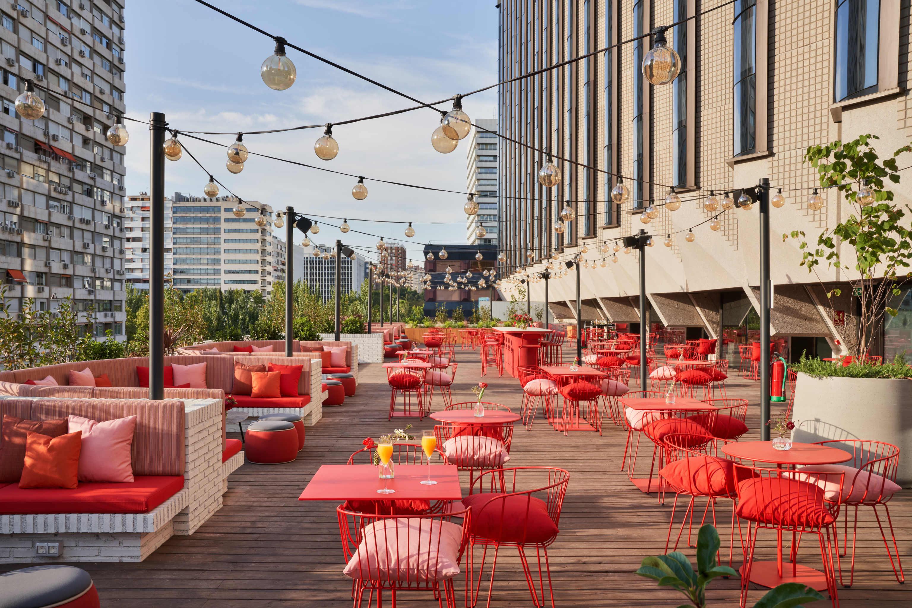 """Numerosas bombillas penden """"de Madrid al cielo"""" en la terraza de este hotel."""