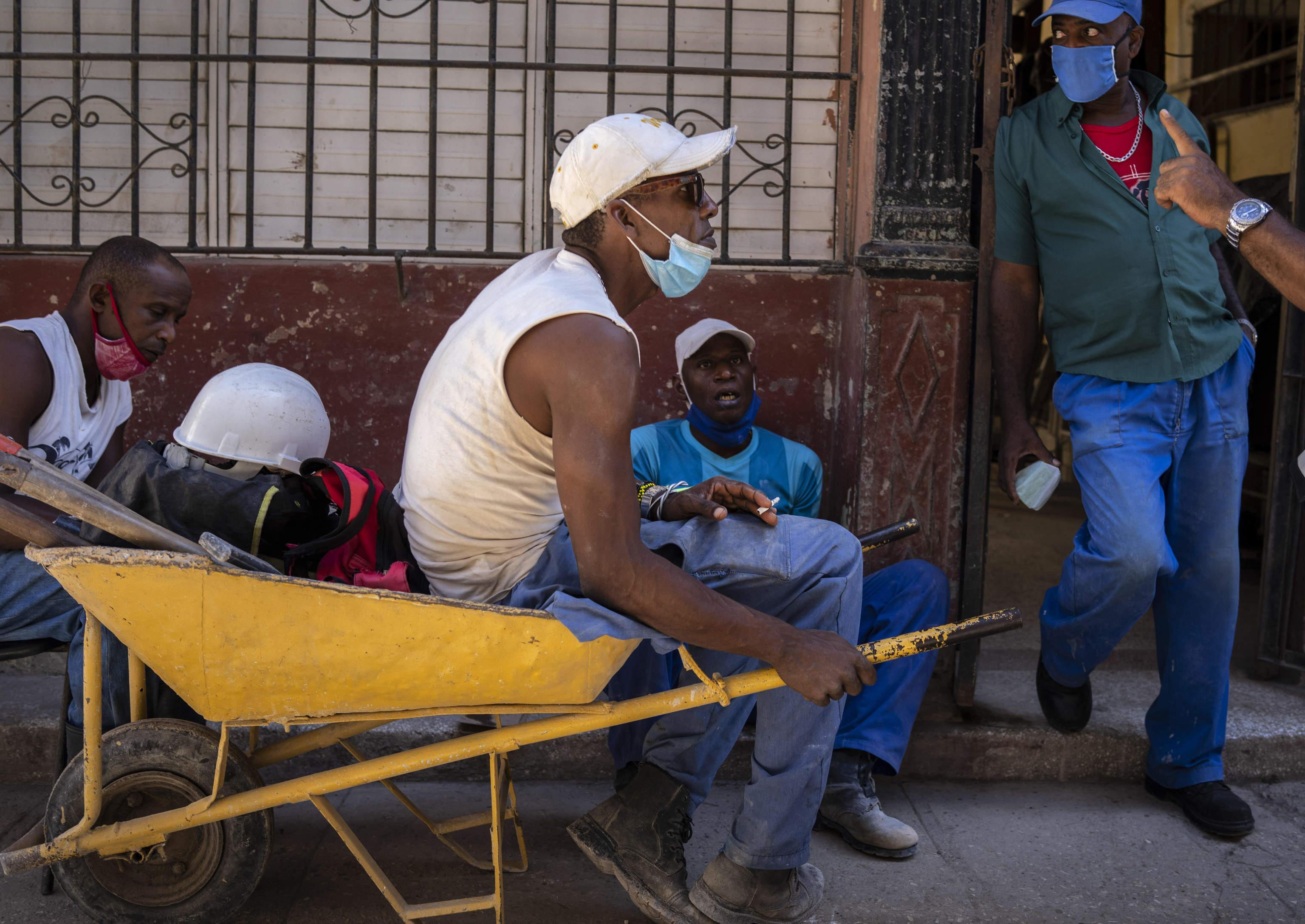 Trabajadores con mascarilla en una calle de La Habana.