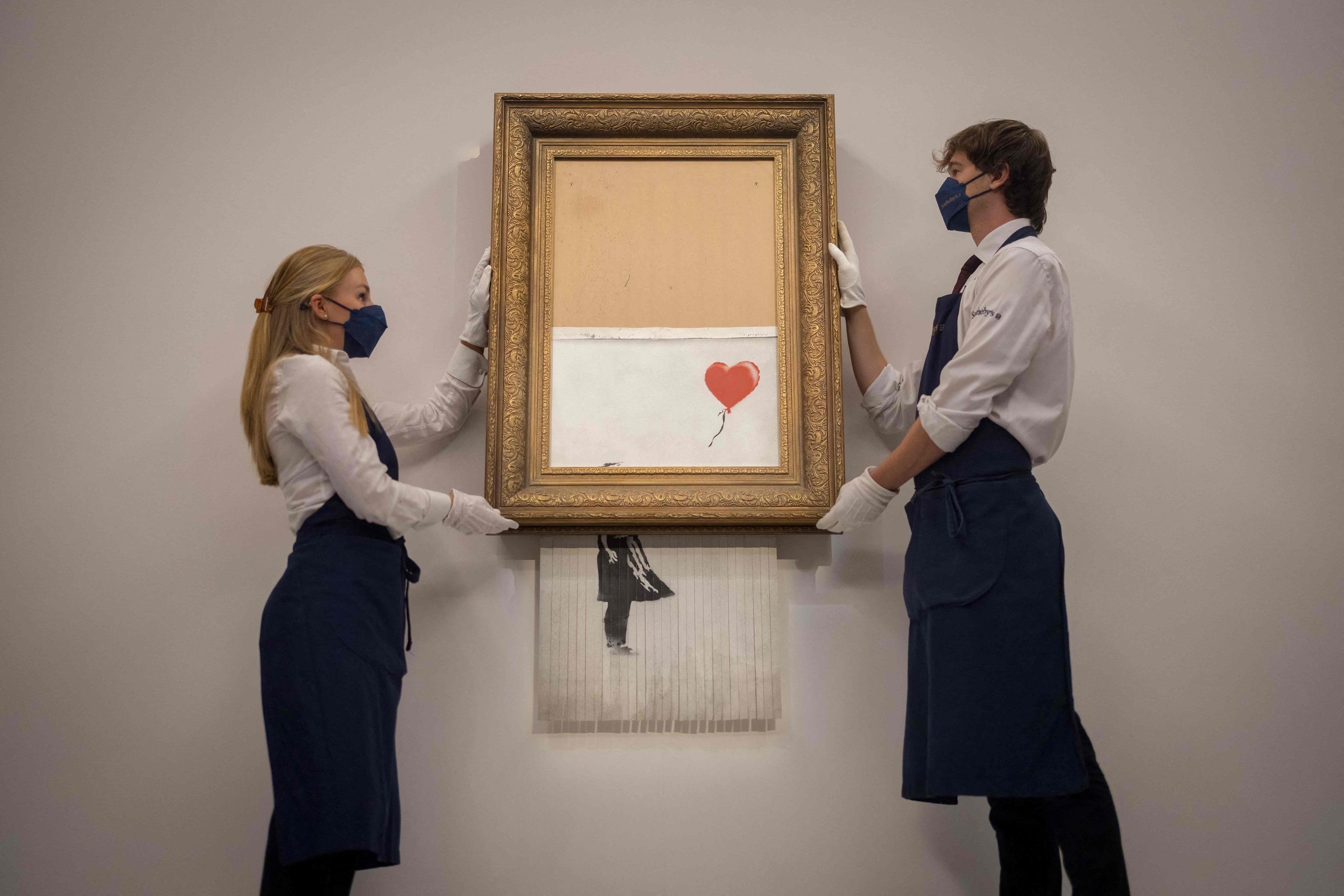 """En esta foto de archivo tomada el 3 de septiembre de 2021 unos asistentes posan junto a una obra de arte titulada """"Love is the Bin"""" del artista callejero británico Banksy durante un photocall en la casa de subastas Sotheby's en el centro de Londres."""