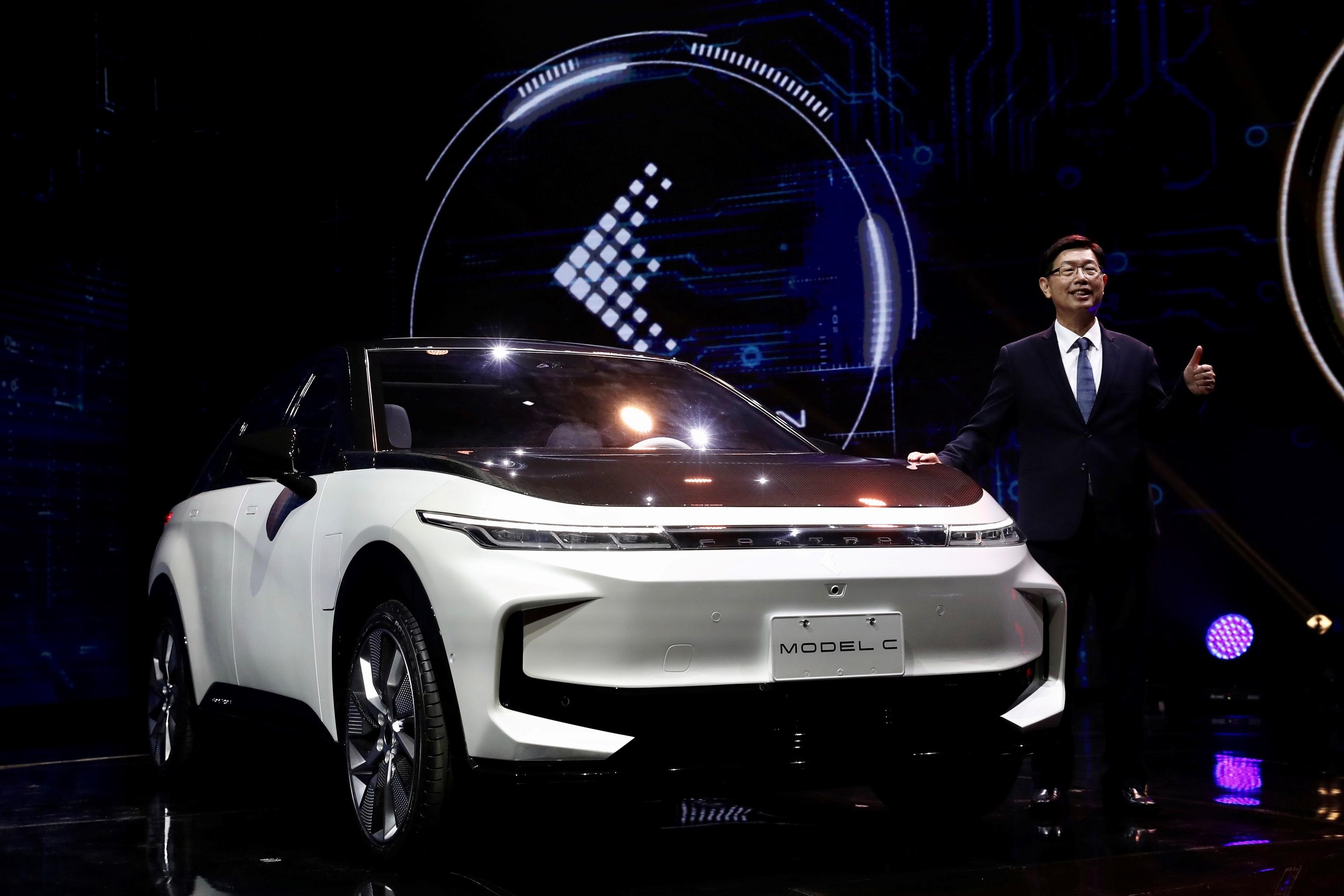 El presidente de Foxxconn, Young Liu, posa junto al Model C, que estaría listo para comercializarse en 2023 por unos 30.000 euros.