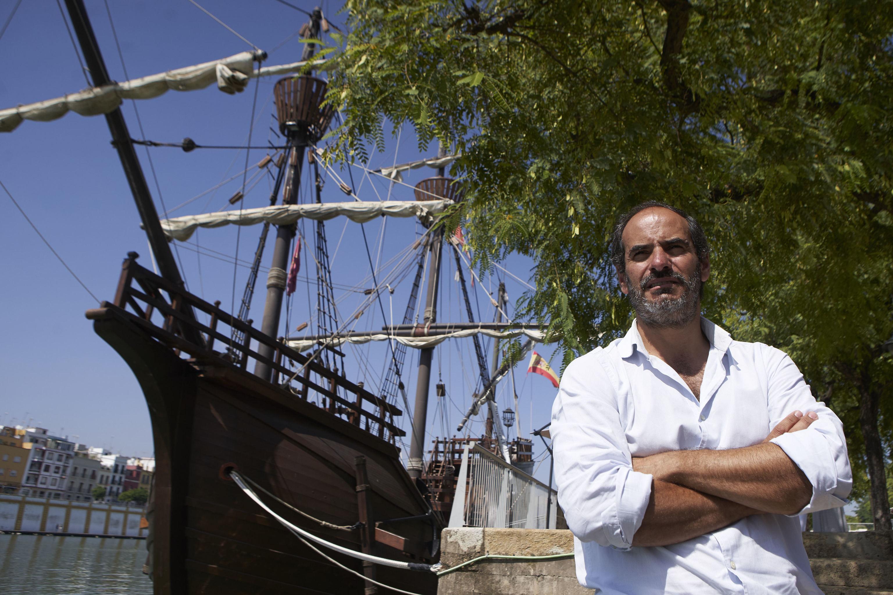 Antonio F.Torres, junto a una réplica de la nao Victoria en el río Guadalquivir a su paso por Sevilla.