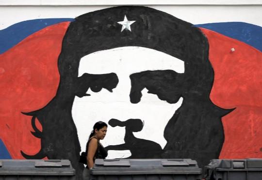 Una mujer camina frente a un mural con el rostro del Che. Reuters