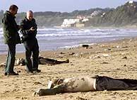Los cadáveres de dos inmigrantes procedentes de la patera de Rota, en la playa de El Buzo. (EFE)