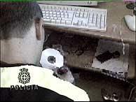 Un agente, con uno de los CD incautados durante la operación. (EFE)