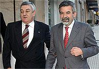 Xesús Palmou (dcha.) llega con el presidente del PP coruñés, Jesús Almuiña, a la sede del partido en Santiago. (EFE)