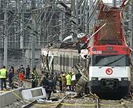 Agentes de policía analizan los restos de uno de los trenes atacados. (AP)