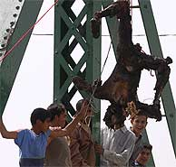 Jóvenes iraquíes, junto a un cadáver carbonizado y colgado de un puente. VEA MÁS IMÁGENES. (AFP)