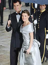 El Príncipe y Letizia se resguardan bajo un paraguas. (AP) VEA MÁS IMÁGENES