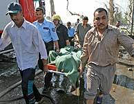 Uno de los muertos en los atentados con coche bomba es evacuado. (REUTERS)