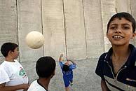 Niños palestinos juegan al fútbol junto al Muro. (EFE)