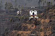 Helicópteros trabajan en la zona arrasada. (AFP)