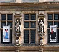 Las imágenes de los periodistas retenidos cuelgan del Ayuntamiento de París con una petición: 'Liberadlos'. (AFP)