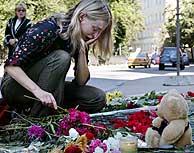 Una mujer llora junto a las flores depositadas en honor a las víctimas. Vea MÁS IMÁGENES. (AP)