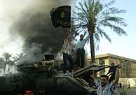 Varios iraquíes bailan junto a un tanque de EEUU en llamas. (AFP)
