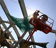 Dos operarios desmontan el recinto. (EFE)