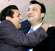 Un militante saluda a Cobo a su llegada a la oficina del PP en Latina. (EFE)