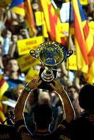 Iván Tubau, capitán de la selección, ofrece el trofeo a los aficionados. (EFE)