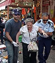 Una mujer herida es evacuada del mercado de Hakarmel. (REUTERS)