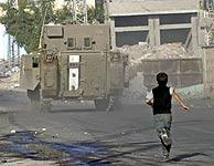 Un niño palestino tira piedras a un tanque israelí en Jenin. (EFE)