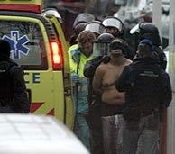 Miembros de las fuerzas antiterroristas junto a uno de los detenidos. (AP)