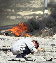 Un niño palestino se agacha para evitar las balas israelíes, en Ramala. (Foto: AP)