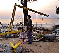 Un padre y su hija observan una de las playas afectas en Phuket (Tailandia). (Foto: AP)