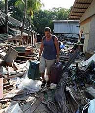 Un turista inglés camina entre las ruinas de su hotel en Pathong, cerca de Phuket. (Foto: REUTERS). VEA MÁS IMÁGENES