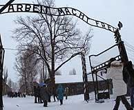 """Visitantes pasan por la entrada del campo, bajo el lema """"El trabajo os hará libres"""". (REUTERS)"""