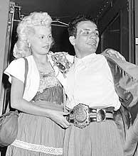 El boxeador Jake LaMotta y su esposa Vicki bajan de un tren en junio de 1949