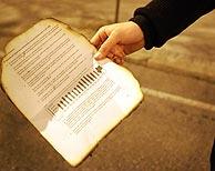 Un documento quemado procedente del edificio incendiado, recogido en la calle. (Foto: EFE)