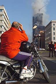 Decenas de ciudadanos rodean el perímetro acordonado del incendio para observar el fuego. (Foto: EFE)