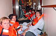 Algunos pasajeros del 'Grand Voyager' esperando en el interior del barco a ser atendidos por los equipos sanitarios. (Foto: EFE)