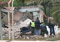 Agentes de los TEDAX inspeccionan el lugar donde estalló el artefacto. (Foto: EFE)