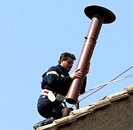 Un operario coloca la chimenea en el tejado de la Capilla Sixtina. (Foto: AP)