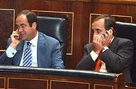 Los ministros Bono y Alonso hablan por el móvil durante la sesión. (Foto: EFE)