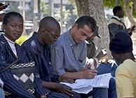 Varios inmigrantes rellenan sus papeles. (Foto: EFE)