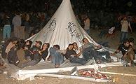 Algunos de los asistentes descansan a la espera de que se reanudasen los conciertos. (Foto: EFE)