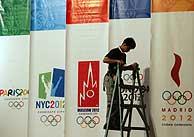 Un trabajador singapureño coloca las banderas de las candidaturas en el hotel de convenciones Raffles. (Foto: AP)