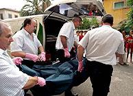 Trabajadores de la funeraria transportan los cuerpos de las víctimas. (Foto: EFE)