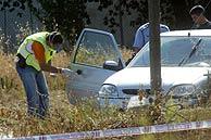 Agentes de la Policía inspeccionan el vehículo de la víctima. (Foto: EFE)