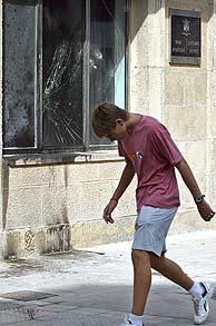 Un joven pasa frente a la fachada del juzgado de Paz de Amorebieta, ennegrecida y con ventanas rotas. (Foto: EFE)