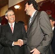 El nuevo presidente de la Xunta es felicitado por el que será su vicepresidente, Quintana. (Foto: EFE)
