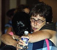 UNa mujer abraza a un familiar que viajaba en el avión. (Foto: AP)