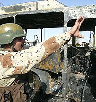 Un soldado iraquí junto a un autobús destrozado por los atentados. (Foto: AF)