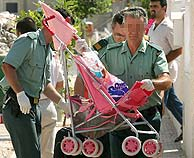 Agentes de la Guardia Civil extraen efectos personales de la vivienda. (Foto: EFE)