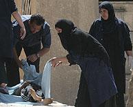 Los familiares buscan y cubren a sus muertos entre la multitud. (Foto: AFP)