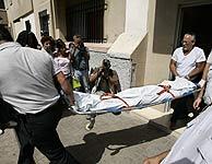 Los servicios funerarios retiran el cadáver de la joven asesinada. (Foto: EFE)