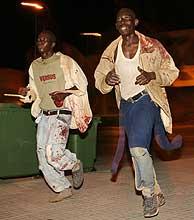 Dos inmigrantes, con las camisas ensangrentadas, corren hacia Melilla tras atravesar la valla. (Foto: REUTERS)