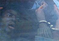 Uno de los subsaharianos que viaja en uno de los convoyes pide ayuda por la ventana. (AFP)