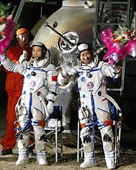 Los astronautas Fei Junlong (izq.) y Nie Haisheng saludan tras bajar de la nave. (Foto: AFP)